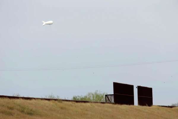 A tethered aerostat uses its radar near La Joya to watch for low-flying aircraft. A section of the U.S. border fence was built in this area.