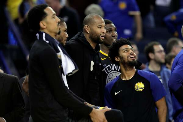 DeMarcus Cousins watches from the bench with teammates as the Warriors pull away late in the second half as the Golden State Warriors played the New Orleans Pelicans at Oracle Arena in Oakland, Calif., on Wednesday, January 16, 2019.