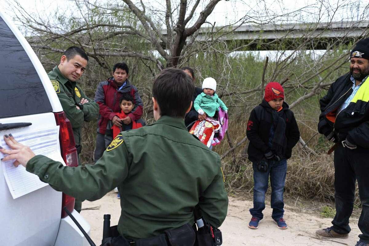 U.S. Border Patrol Agents Marcelino Medina, 44, left, and Sarah Arias, 25, foreground, process Honduran immigrants who surrendered upon entering the U.S. by the Anzalduas International Bridge in Hidalgo County, Monday, Feb. 12, 2018.