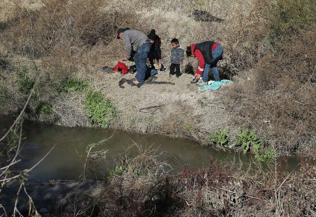 EL PASO, TEXAS - JANUARY 13: A man from Honduras and a woman and her children from Guatemala put dry clothes on as they prepare to turn themselves over to U.S. Border Patrol agents after crossing part of the Rio Grande river from Mexico to ask for an asylum consideration on January 13, 2019 in El Paso, Texas. The U.S. government is partially shutdown as President Donald Trump is asking for $5.7 billion to build additional walls along the U.S.-Mexico border and the Democrats oppose the idea.(Photo by Joe Raedle/Getty Images)