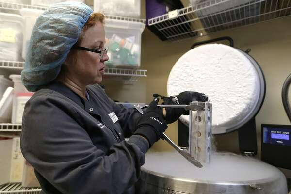 In this Tuesday, Oct. 2, 2018 photo, Kimberly Malm removes a container with frozen embryos and sperm being stored in liquid nitrogen at a fertility clinic in Fort Myers, Fla. Tens of thousands of embryos remain frozen in fertility clinics around the United States, in limbo or abandoned by couples who can't agree or have walked away from deciding what to do with leftovers from pregnancy attempts. (AP Photo/Lynne Sladky)