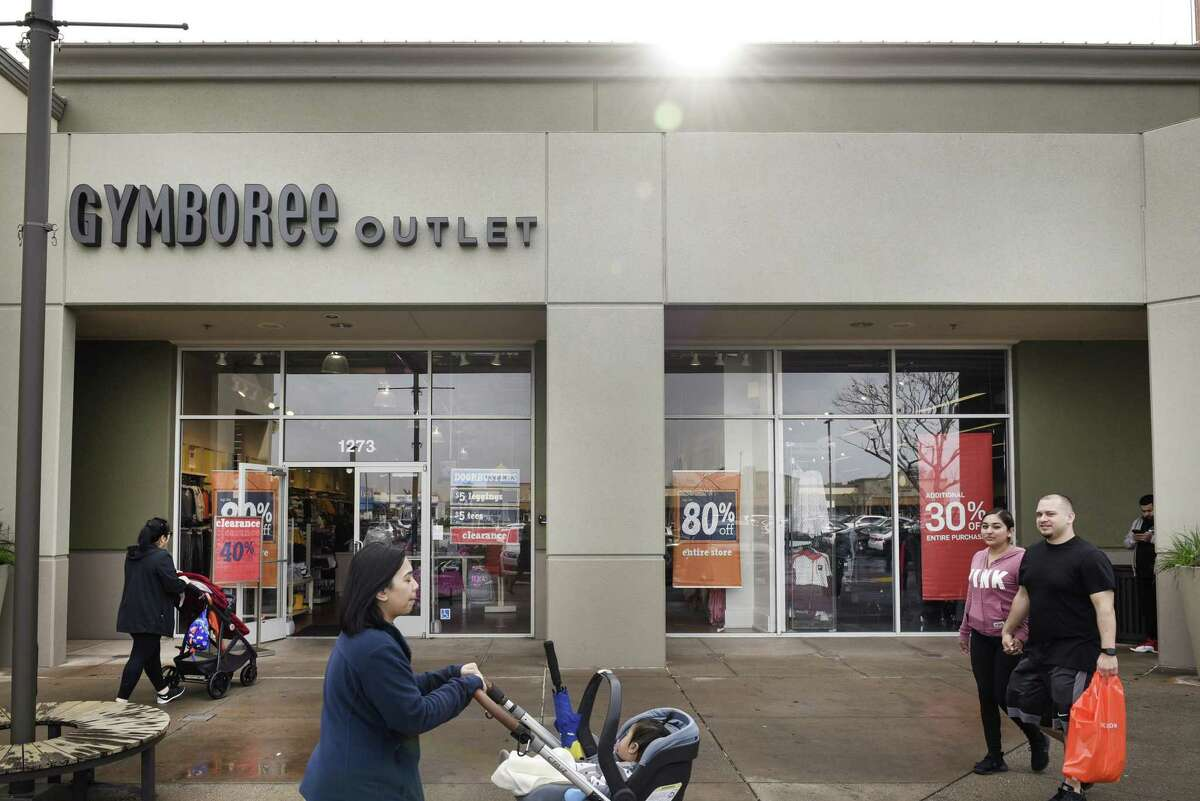People walk past a Gymboree Outlet offering store-wide discounts, in San Leandro, CA, on Thursday January 17, 2019. Gymboree Group filed for chapter 11 bankruptcy late Wednesday and is planning to close all its Gymboree and Crazy 8 brand stores. Its intellectual property, Gymboree?•s online platform and its higher-end Janie and Jack line is being sold to Special Situations Investing Group, an affiliate of Goldman Sachs, pending court approval.