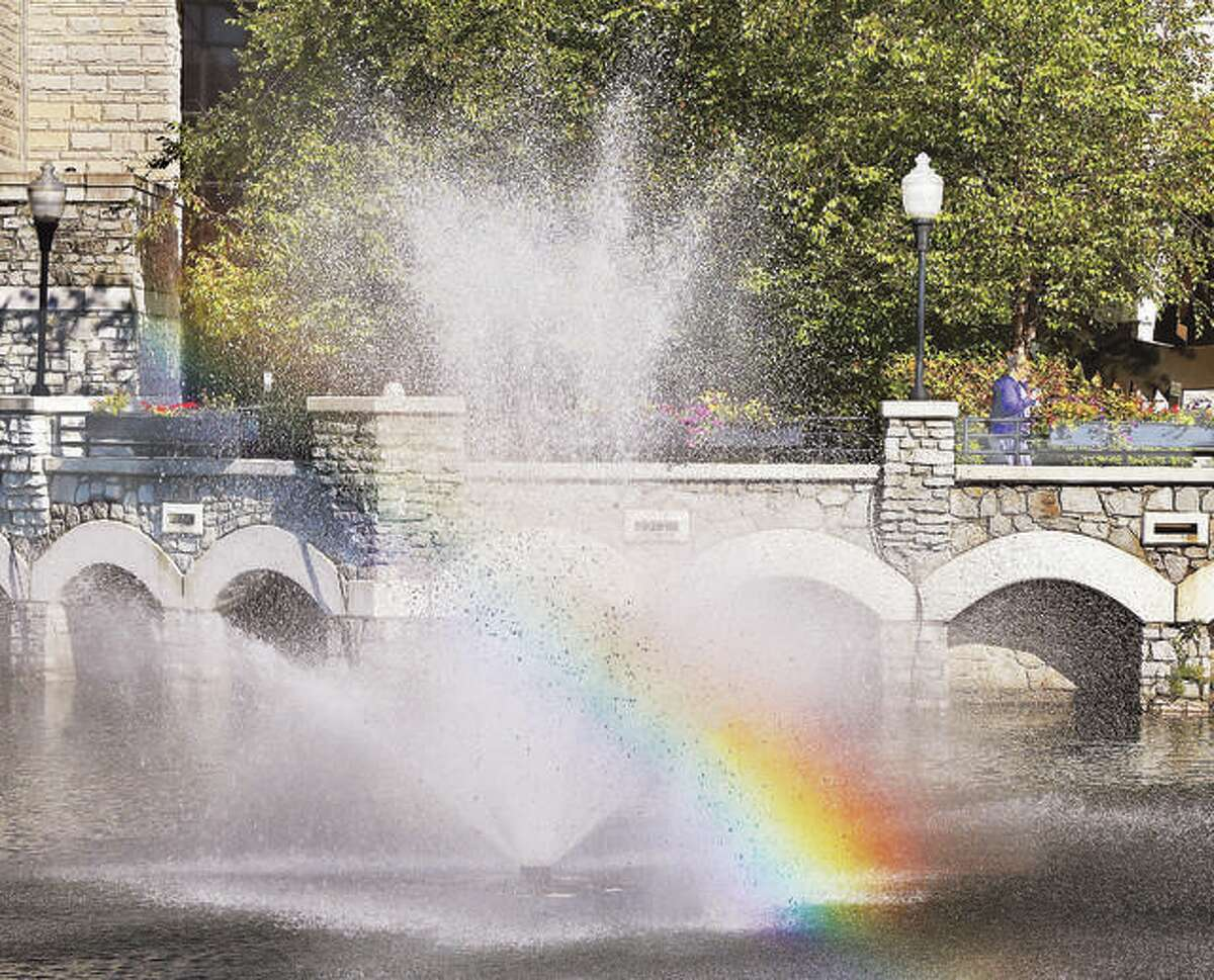 A student at Lewis and Clark Community College, right, leaves classes in bright sunshine past a fountain forming its own rainbow in the water's overspray.