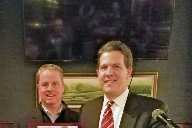 New Canaan Exchange Club President Jeff Platt, left, accepts the Community Cornerstone Award from HomeFront Executive Director Sean O'Brien during a recent meeting held at Woodway Country Club.