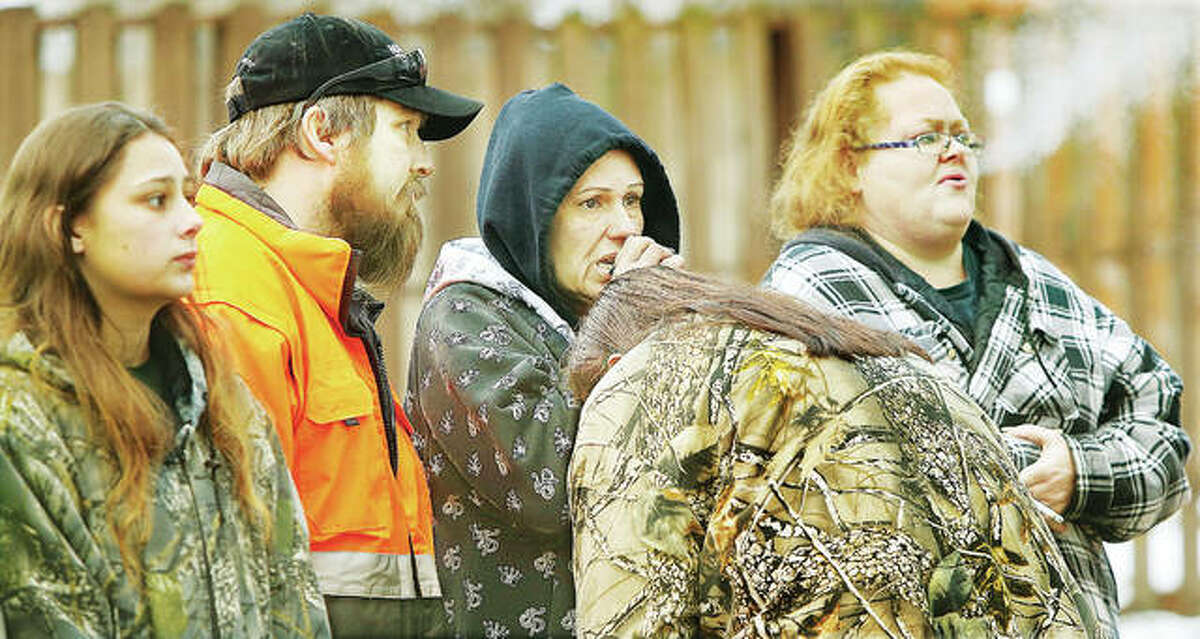 Emotional family and friends watch firefighters sift through the rubble in the early morning cold.