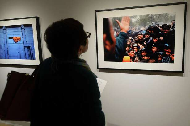 Westport resident Roseanne Spengler looks at the exhibit by and Westport native Getty photojournalist Spencer Platt, Fractured, Friday, January 11, 2019, at the Westport Arts Center in Westport, Conn. The show runs through March 3rd.