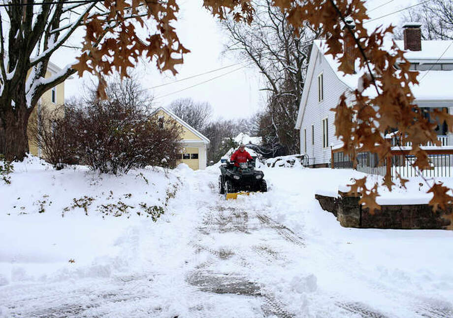 An ATV with a snow plow attached is used to clear a driveway on Hickory Street in Edwardsville last weekend. Photo: Marci Winters-McLaughlin | For The Intelligencer