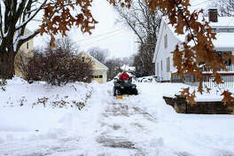 An ATV with a snow plow attached is used to clear a driveway on Hickory Street in Edwardsville last weekend.