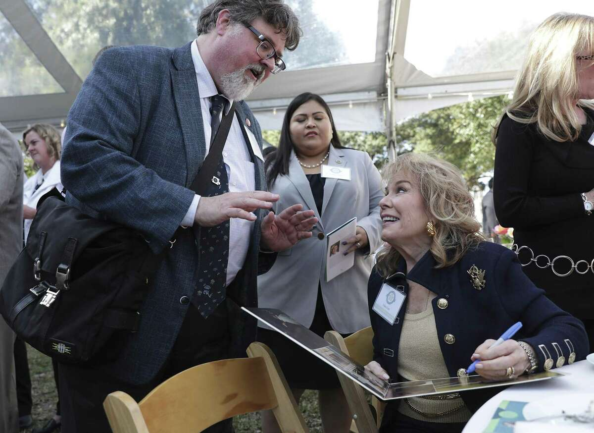 Vikki Carr, right, signs a record album for Stephen Ray, Texas Music Office Program Specialist, after Carr was inducted into the Texas Women's Hall of Fame at the Governor's Mansion in Austin, on Thursday, Jan. 17, 2019.