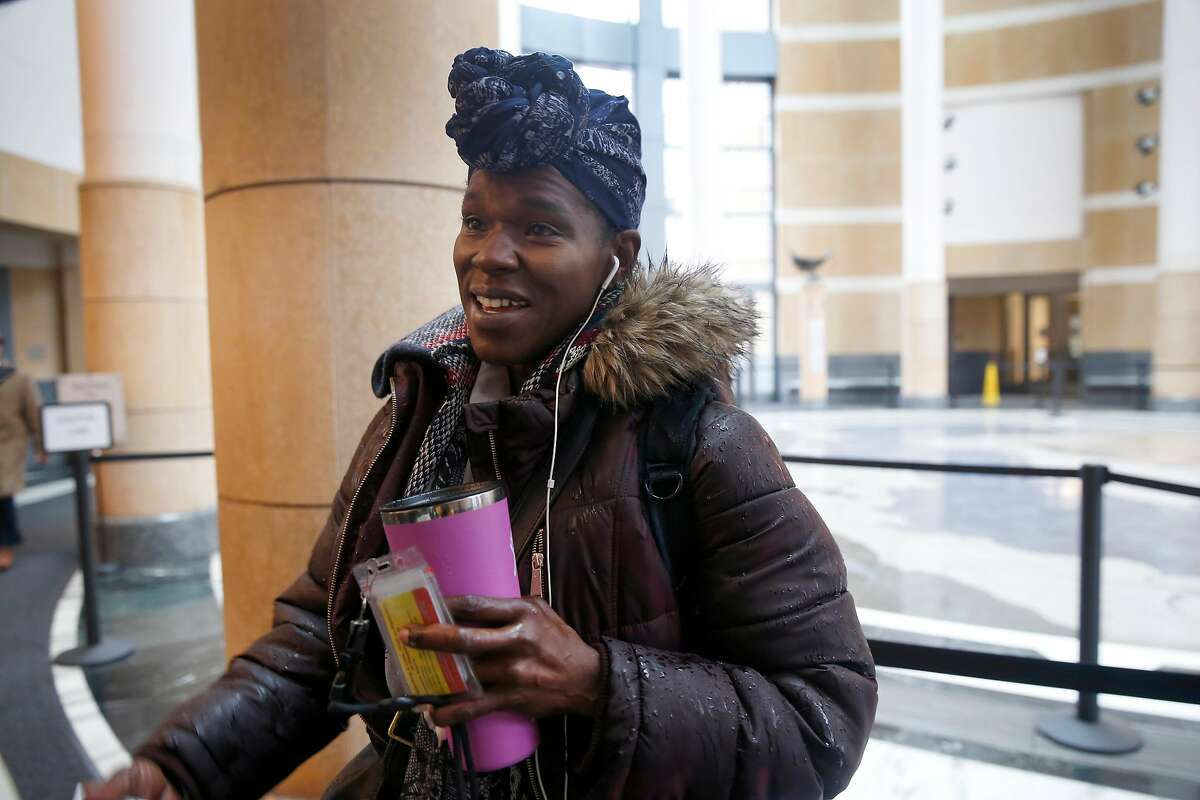 """An Internal Revenue Service employee, who declined to give her name, reports for work at the Ronald Dellums Federal Building in Oakland, Calif. on Thursday, Jan. 17, 2019. Despite being unpaid during the partial government shutdown, the woman described herself as """"a happy employee of the federal government."""""""