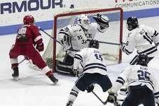 Yale's Corbin Kaczperski makes a glove save against Sacred Heart.