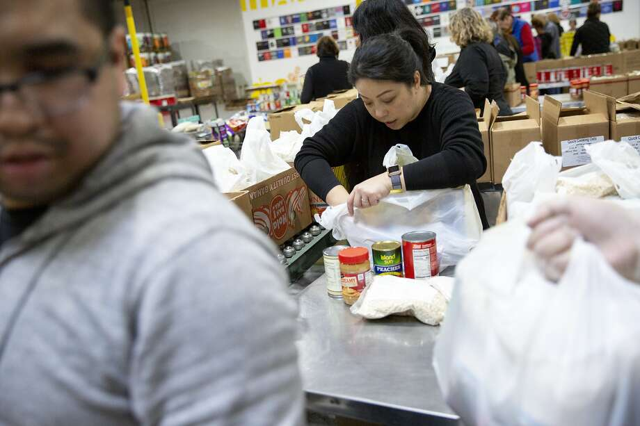 Volunteer Amy Poon packs food bags at the Alameda County Community Food Bank on Thursday, Jan. 17, 2019, in Oakland, Calif. The food bank is delivering more than 1,000 food bags to TSA agents, 300 Alameda Coast Guard families, workers at the Department of Corrections and others. Considered an emergency response, the food bank is dipping into food reserves and bringing in extra volunteers and plans to continue as long as needed during the government shutdown and furlough of government employees. Photo: Santiago Mejia / The Chronicle