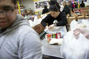 Volunteer Amy Poon packs food bags at the Alameda County Community Food Bank on Thursday, Jan. 17, 2019, in Oakland, Calif. The food bank is delivering more than 1,000 food bags to TSA agents, 300 Alameda Coast Guard families, workers at the Department of Corrections and others. Considered an emergency response, the food bank is dipping into food reserves and bringing in extra volunteers and plans to continue as long as needed during the government shutdown and furlough of government employees.