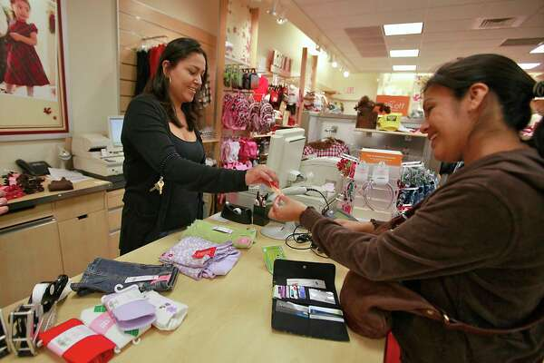 FILE - In this Monday, Oct. 4, 2010, file photo, Susi Ortiz, right, buys children's clothing at the Gymboree store at the Westside Pavilion Shopping Center in Los Angeles. Children?s clothing retailer Gymboree has filed bankruptcy protection for a second time in as many years and will begin winding down all operations. The San Francisco company said late Wednesday, Jan. 17, 2019, that it will close all of its Gymboree and Crazy 8 stores, and will to sell its Janie and Jack business, intellectual property and online business. (AP Photo/Damian Dovarganes, File)