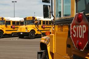 Busses in the Northside Independent School District sit in preparation for the first day of school in this 2004 file photo. Both Northside and North East ISDs are offering to expedite hiring of furloughed government employees as bus drivers and substitute teachers. (Robert McLeroy/Staff)