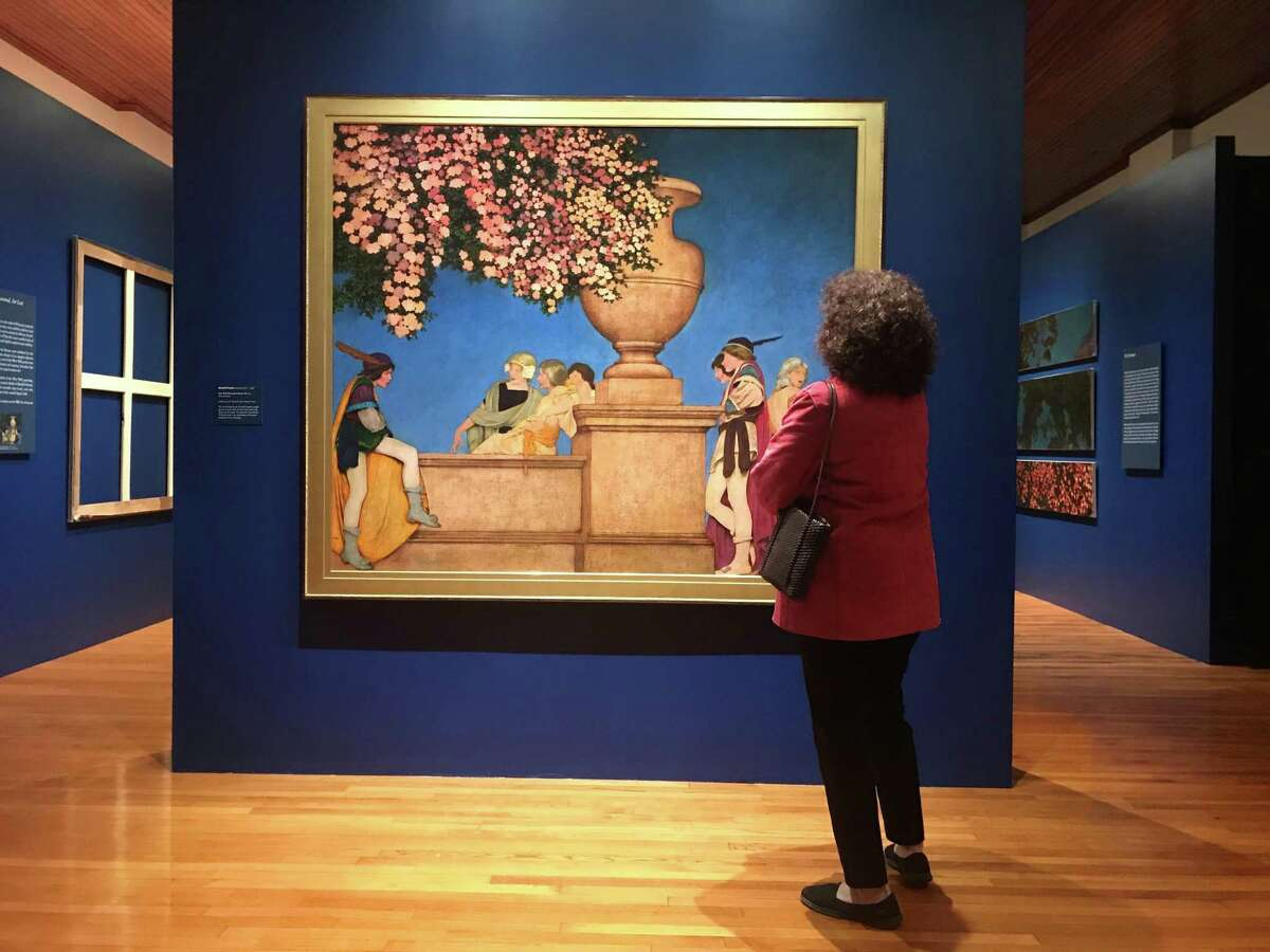 Barbara Canetti admires one of the murals Maxfield Parrish created for the studio of Gertrude Vanderbilt Whitney from 1914 to 1918; two of the six originals were stolen from a Los Angeles gallery in 2001, and the frames the thieves left are included in a show of the murals at Galveston's Bryan Museum.