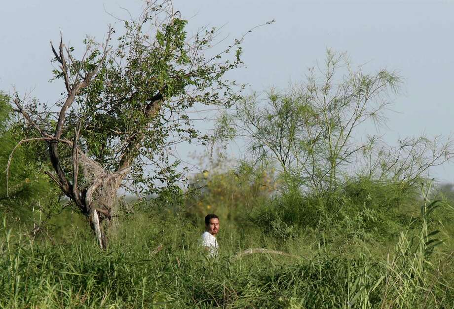 A man on the Mexican side of the Rio Grande watches Border Patrol agents at a known smuggling point near Penitas, Texas. Photo: JERRY LARA, San Antonio Express-News / San Antonio Express-News