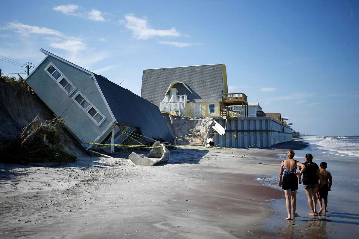 FILE-- A home collapsed onto the beach during Hurricane Irma, in Vilano Peach, Fla., Sept. 14, 2017. Many of the big economic questions in coming decades will come down to just how extreme the weather will be, and how to value the future versus the present. (Luke Sharrett/The New York Times)