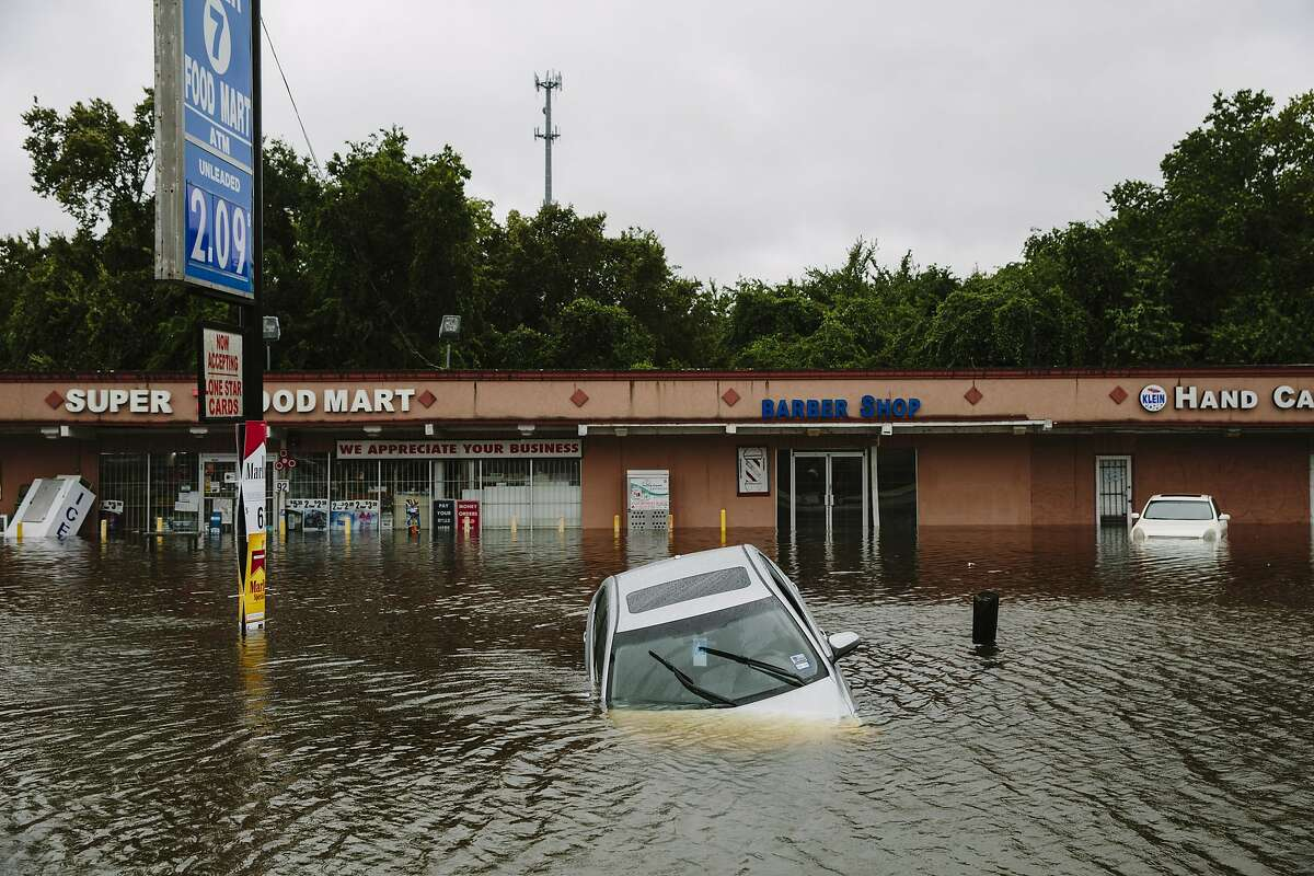 FILE-- A flooded car along Kuykendahl Road after Hurricane Harvey swept through through Houston, Aug. 29, 2017. Many of the big economic questions in coming decades will come down to just how extreme the weather will be, and how to value the future versus the present. (Edmund D. Fountain/The New York Times)