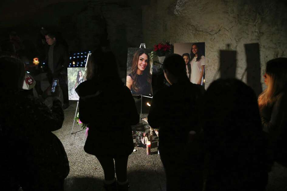 Friends and family gather in front of portraits of Nichol Olsen and her two daughters during a vigil at the Oblate Mission Lourdes Grotto on Wednesday. Olsen, 37, and her two daughters, Alexa Denise Montez, 16, and London Sophia Bribiescas, 10, were found shot to death at a home near Leon Springs last week.