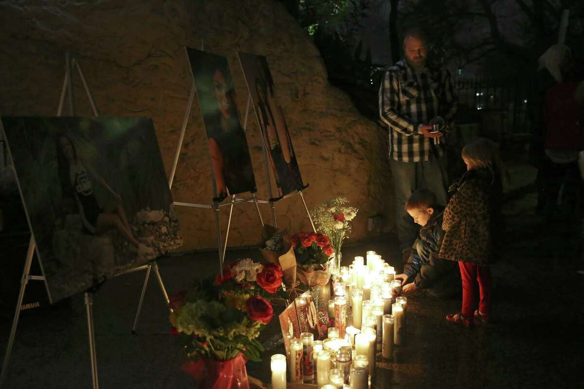 Andy Cerwin and his children, Landon, 8, and Madison, 4, pay their respects during a vigil for Nichol Olsen and her two daughters at the Oblate Mission Lourdes Grotto on Jan. 16. Olsen, 37, and her two daughters, Alexa Denise Montez, 16, and London Sophia Bribiescas, 10, were found shot to death at a home near Leon Springs last week.