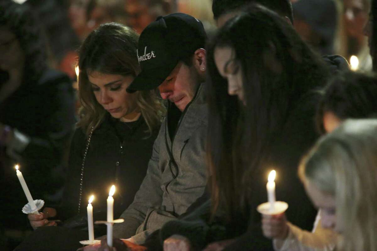 Friends and family gather during a vigil for Nichol Olsen and her two children at the Oblate Mission Lourdes Grotto on Jan. 16. The candlelight vigil honored Olsen, 37, and her two daughters, Alexa Denise Montez, 16, and London Sophia Bribiescas, 10, who were found shot to death at a home near Leon Springs last week.
