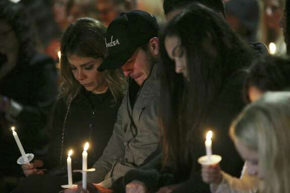 Friends and family gather during a vigil for Nichol Olsen and her two children at the Oblate Mission Lourdes Grotto on Wednesday. The candlelight vigil honored Olsen, 37, and her two daughters, Alexa Denise Montez, 16, and London Sophia Bribiescas, 10, who were found shot to death at a home near Leon Springs last week.