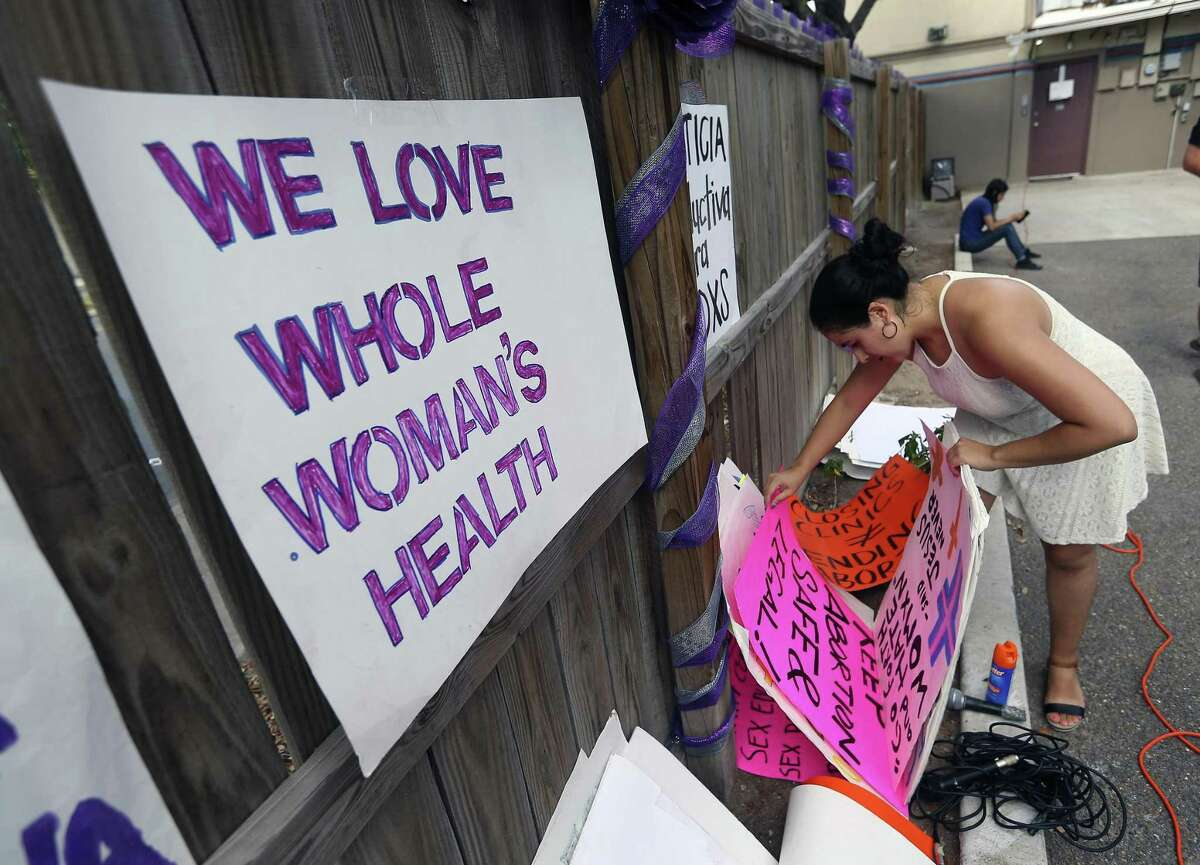 Sofia Pena decorates a fence with signs before a news conference and rally June 27, 2016, at the Whole Woman's Health clinic in McAllen. Some people gathered at the clinic to celebrate the U.S. Supreme Court's 5-3 ruling that struck down several Texas abortion regulations, sparing nearly a dozen clinics in the state from imminent closure.