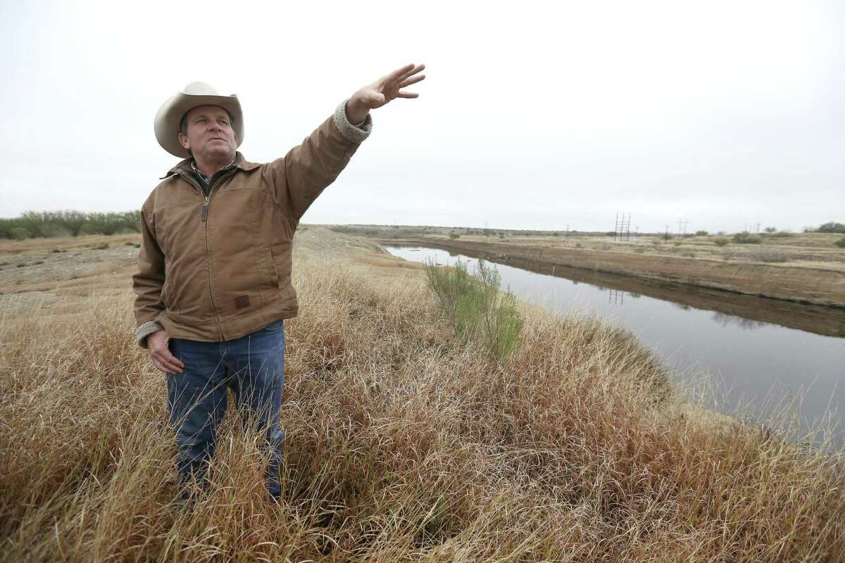 Jason Peeler stands next to an abandoned lignite surface mine on his family's ranch Wednesday, Jan. 16, 2018, that has filled with water as he shows visitors to the ranch damage he says has been caused to parts of the property by San Miguel Electric Cooperative's coal-burning power plant and lignite mining operations.