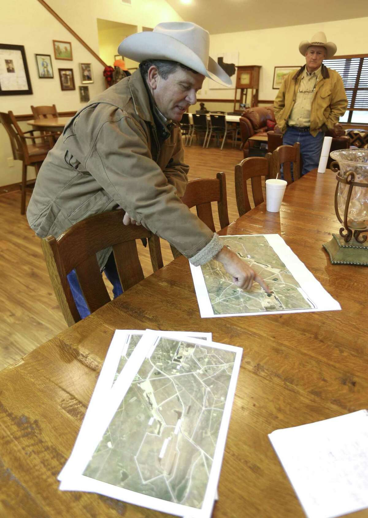 Jason Peeler points to maps of his family's ranch Wednesday, Jan. 16, 2018, as he tells visitors to the ranch about damage he says has been caused to parts of the property by San Miguel Electric Cooperative's coal-burning power plant.