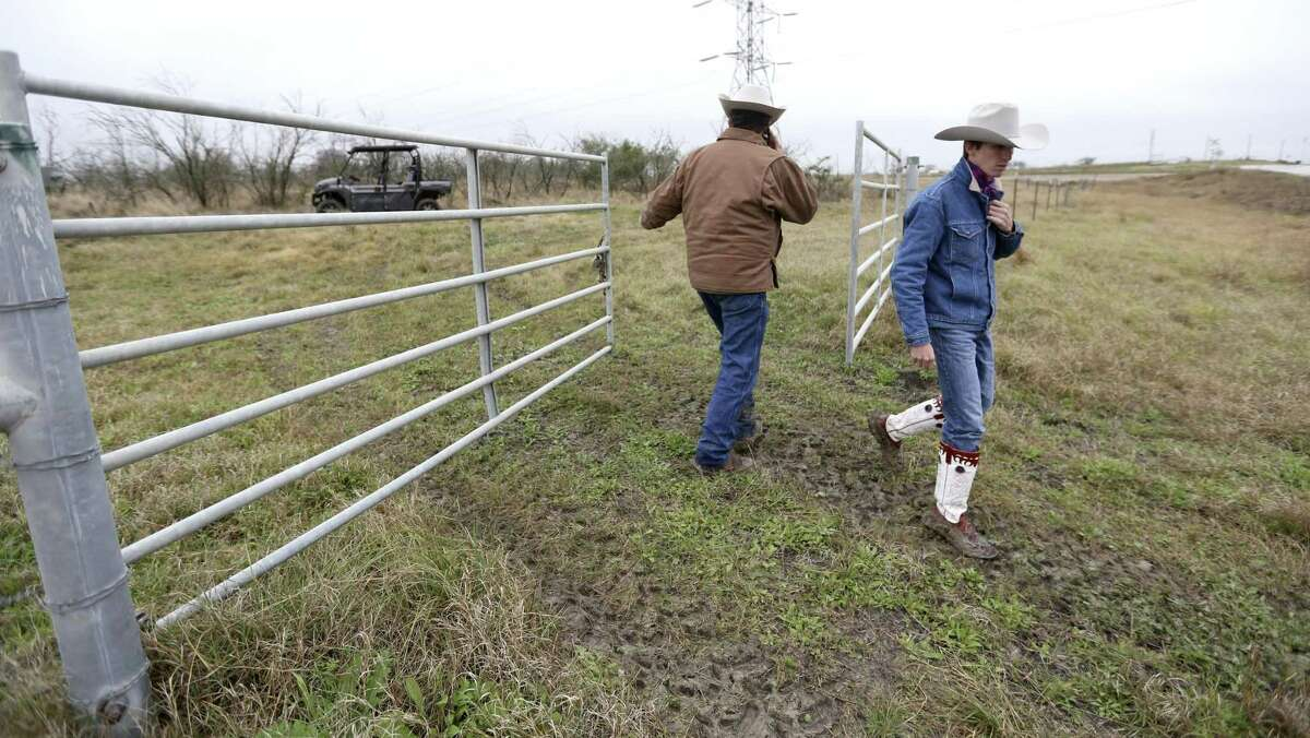 Jason Peeler left, closes a gate on his ranch Wednesday, Jan. 16, 2018, after he and his son, Ben, passed through. The Peelers were showing visitors to the ranch damage they says has been caused to parts of the property by San Miguel Electric Cooperative's coal-burning power plant and lignite mining operations.