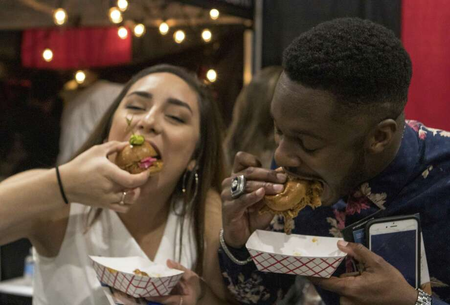 The Woodlands residents Victoria Salazar, left, and Marcus Stallings take a bite from sliders they received during the 33rd annual Taste of the Town on Thursday, Jan. 17, 2019 at The Woodlands Waterway Marriott Hotel & Convention Center. Photo: Cody Bahn, Houston Chronicle / Staff Photographer / © 2018 Houston Chronicle