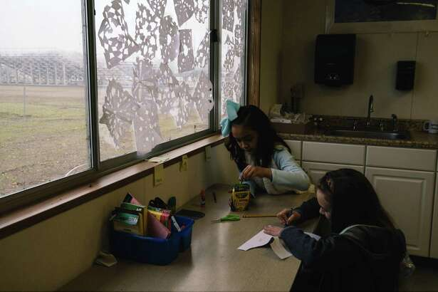 Fifth-graders Destiny Hutchison and Maria Brodie, both 10, work on class assignments at Durham Elementary School, which opened its doors to students from Ponderosa Elementary School after the Camp Fire.
