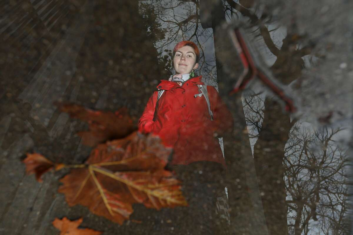 Leigh Honeywell of San Francisco is seen reflected in a puddle of water with leaves as she stands for a portrait on Battery Street on Thursday, January 17, 2019 in San Francisco, Calif. Honeywell slipped on a wet pile of leaves in 2015 on Battery Street on her way to see a show at the Punchline.