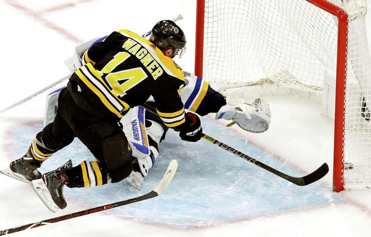 Boston Bruins right wing Chris Wagner (14) scores past the outstretched glove of Blues goaltender Jake Allen in the third period Thursday night's game in Boston.