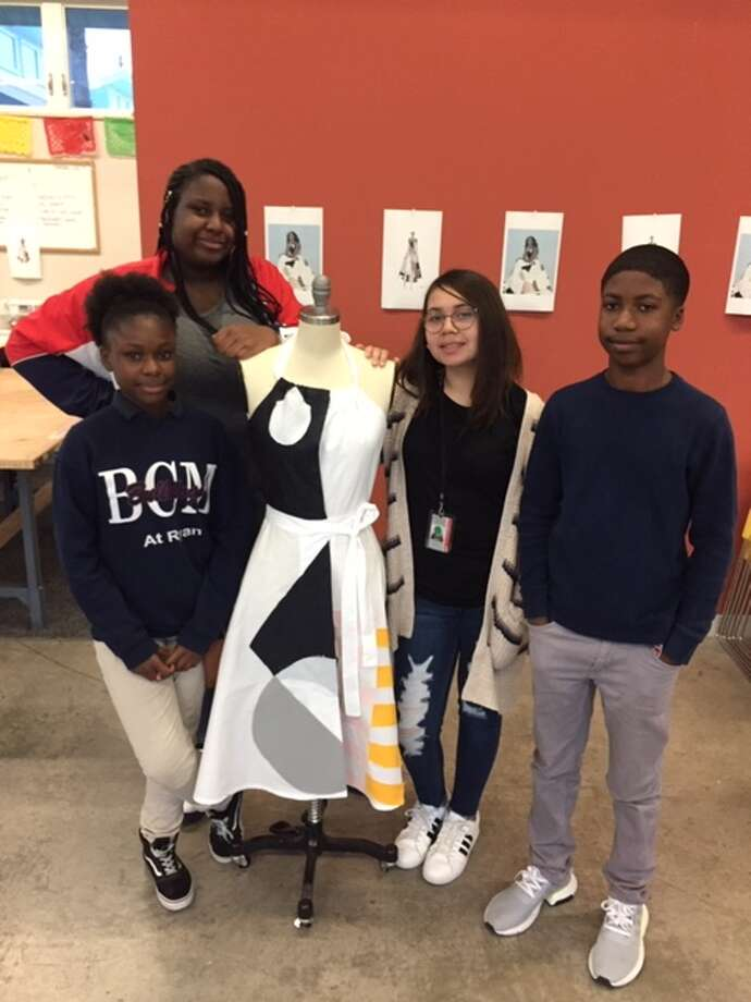 To celebrate former First Lady Michelle Obama's birthday on Jan. 17,  students at Workshop Houston created a dressed inspired by the Milly  dress she wore for the presidential portrait. They are: Jayla Russell,  12, a 7th grader at the Baylor College of Medicine Academy; Talia Bonty,  13, an 8th grader at A Plus UP; Ophelia Dominguez-Morin, 12, a 6th  grader at A Plus UP; and Caleb Harris, 15, a 10th grader at the Energy  Institute High School. Photo: Joy Sewing