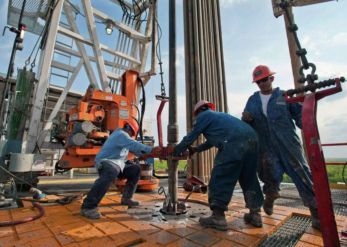 Floor hands Jose Garza, left, Jose Salinas, center, and Omar Cano make a pipe connection on Orion Drilling Co.'s Perseus drilling rig near Encinal in Webb County, Texas.