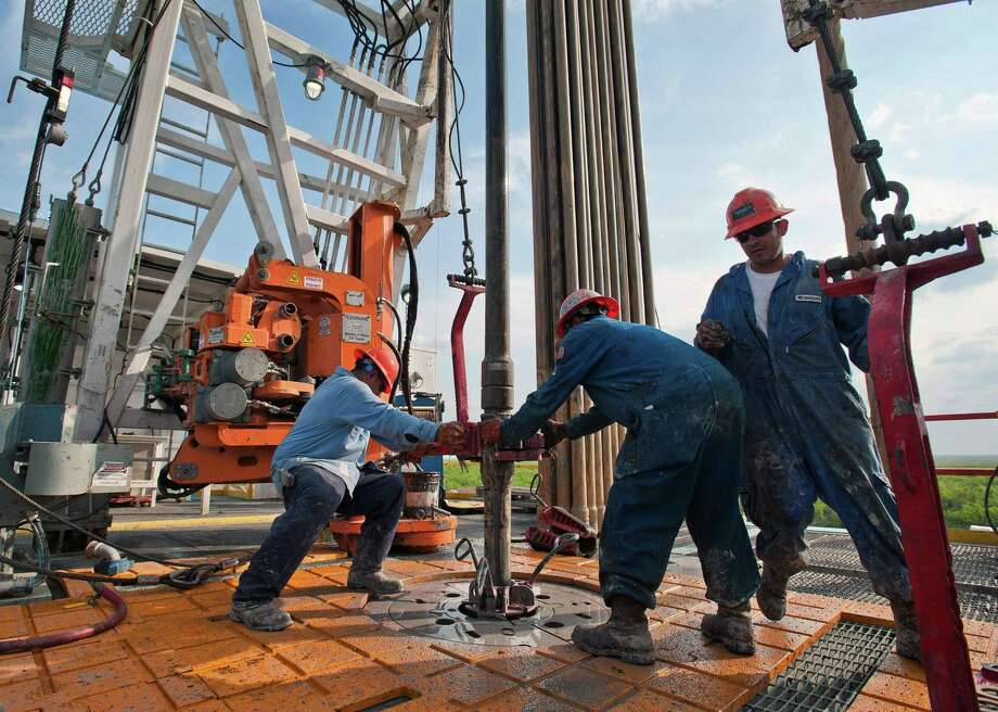 Floor hands Jose Garza, left, Jose Salinas, center, and Omar Cano make a pipe connection on Orion Drilling Co.'s Perseus drilling rig near Encinal in Webb County, Texas. Photo: Eddie Seal / Bloomberg / © 2018 Bloomberg Finance LP