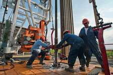Floor hands make a pipe connection on drilling rig in Webb County.
