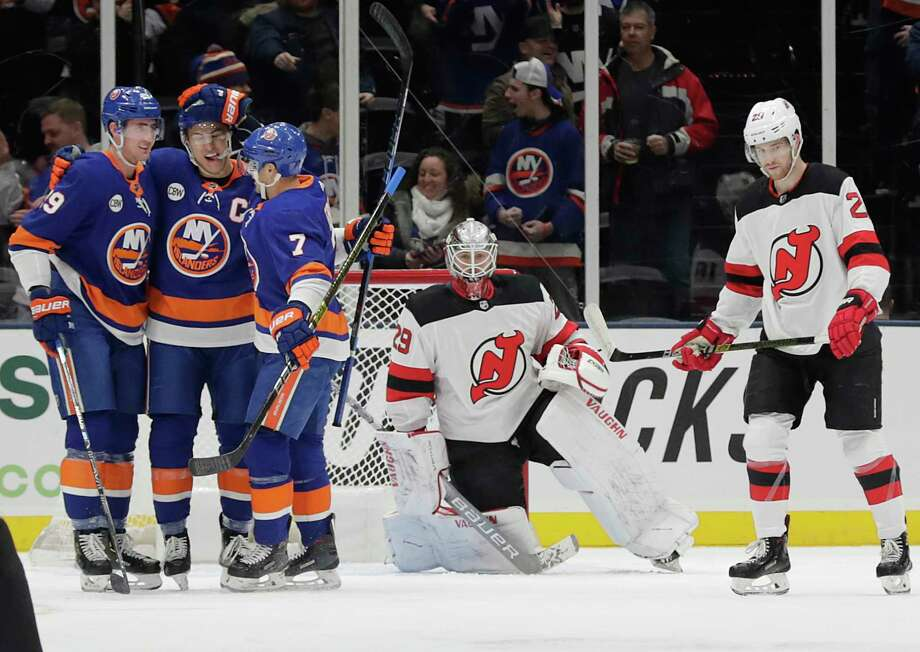 New York Islanders' Brock Nelson (29) and Jordan Eberle (7) celebrate with Anders Lee after Lee scored a goal as New Jersey Devils goaltender Mackenzie Blackwood (29) and Blake Coleman (20) react during the first period of an NHL hockey game, Thursday, Jan. 17, 2019, in Uniondale, N.Y. (AP Photo/Frank Franklin II) Photo: Frank Franklin II / Copyright 2019 The Associated Press. All rights reserved