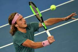 Greece's Stefanos Tsitsipas hits a return against Georgia's Nikoloz Basilashvili during their men's singles match on day five of the Australian Open tennis tournament in Melbourne on January 18, 2019. (Photo by Greg Wood / AFP) / -- IMAGE RESTRICTED TO EDITORIAL USE - STRICTLY NO COMMERCIAL USE --GREG WOOD/AFP/Getty Images