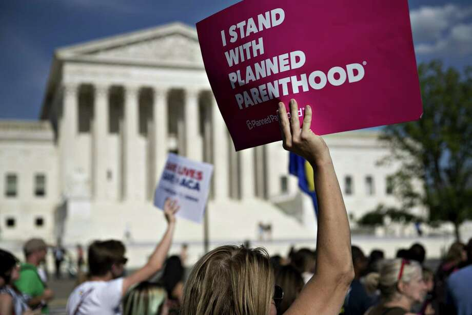 """A demonstrator opposed to the Senate Republican health-care holds a sign that reads """"I Stand With Planned Parenthood"""" while marching near the U.S. Supreme Court in Washington on June 28, 2017. Photo: Bloomberg Photo By Andrew Harrer. / © 2017 Bloomberg Finance LP"""