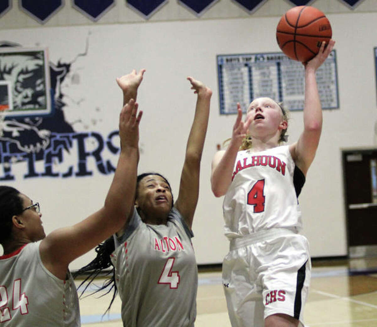 Calhoun's Colleen Schumann (right) shoots over Alton's Germayia Wallace (4) and Deja Carter during a tournament game Dec. 29 in Jerseyville. Calhoun and Alton both sustained losses in conference play Thursday night.