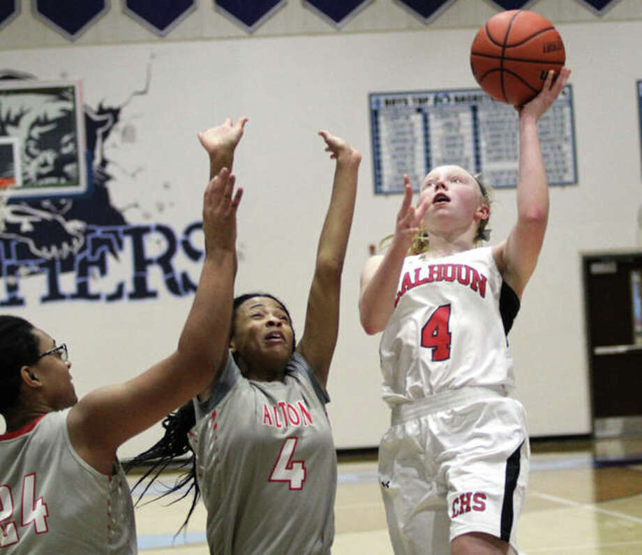 Calhoun's Colleen Schumann (right) shoots over Alton's Germayia Wallace (4) and Deja Carter during a tournament game Dec. 29 in Jerseyville. Calhoun and Alton both sustained losses in conference play Thursday night. Photo: Greg Shashack / The Telegraph