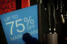 The shadow of a pedestrian is cast on a sale sign displayed at a Gap Inc. store in San Francisco, California, U.S., on Thursday, Jan. 3, 2019. A gauge of Americans' attitudes toward purchases rose to an 18-year high at the end of 2018, helping lift the Bloomberg Consumer Comfort Index for a second week. Photographer: David Paul Morris/Bloomberg