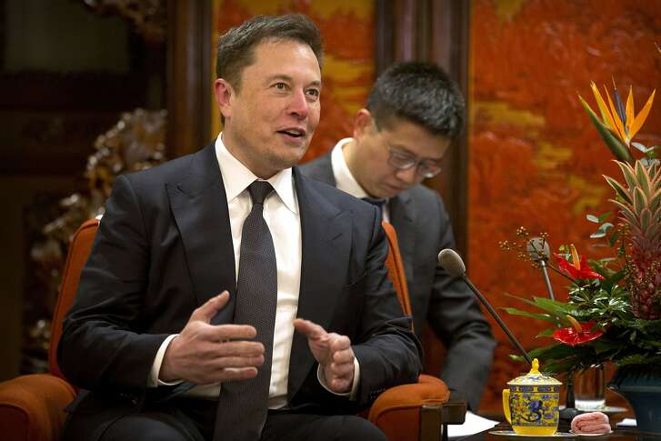 FILE - In this Jan. 9, 2019, file photo, Tesla CEO Elon Musk speaks during a meeting with Chinese Premier Li Keqiang at the Zhongnanhai leadership compound in Beijing. Electric car and solar panel maker Tesla said Friday, Jan. 18, 2019 it plans to cut its staff by about 7 percent. (AP Photo/Mark Schiefelbein, Pool, File)