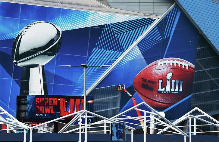 Workers use a lift to install a Super Bowl 53 wrap on the outside of Mercedes-Benz Stadium as it is transformed for the big NFL football game, Thursday, Jan. 17, 2019, in Atlanta. (Curtis Compton/Atlanta Journal-Constitution via AP)