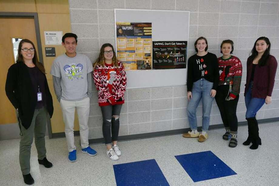 From left to right: Ridgefield High School health teacher Margaret Meriwether stands with seniors Tadd Long, Danielle Butz, Anna Doman, Nikki Rdzanek and Jessica Fine in front of one of the school's anti-vaping posters. The students have been working to combat vaping through creating public service announcements that are posted and shown around the school. January 2019. Photo: Peter Yankowski / Hearst Connecticut Media / The News-Times