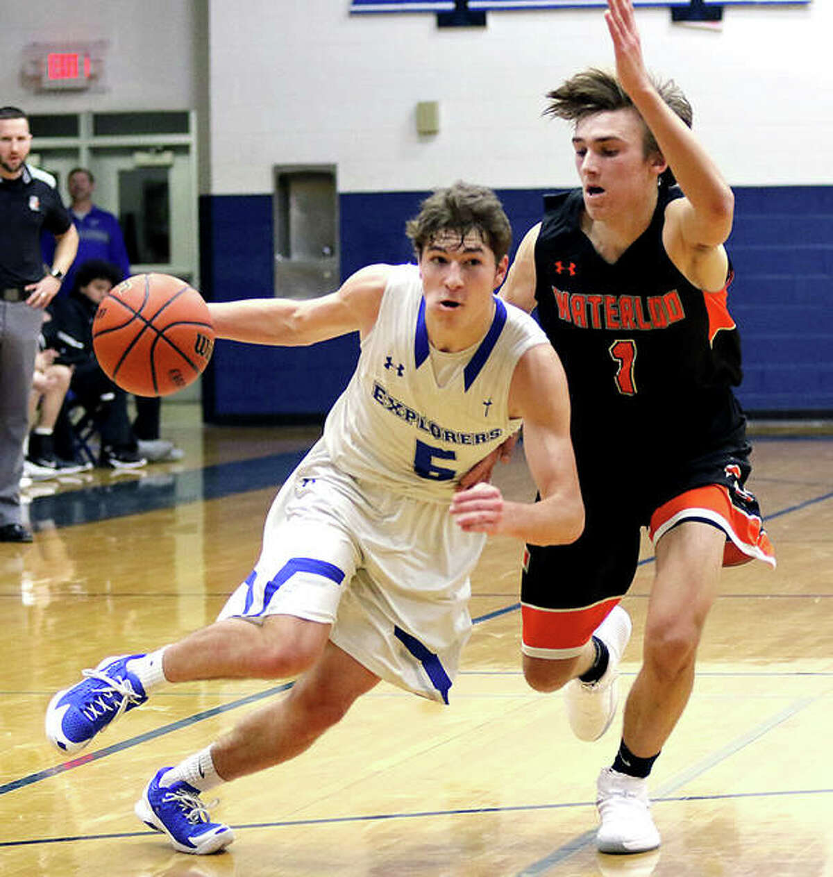 Marquette Catholic's Chris Hartrich (left) drives past Waterloo's Tre Wahlig and converts a three-point play during the second half Thursday night in the Sparta Mid Winter Classic at Dwight Fulton Gym in Sparta.