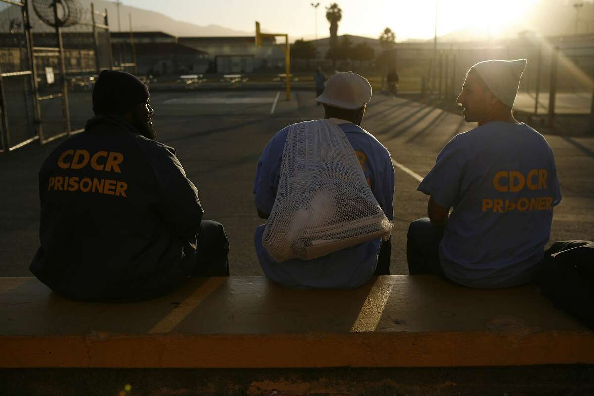 Earlonne Woods, left, Shadeed Wallace-Stepter, center and Adnan Khan, right, watch the sunset on the yard inside San Quentin State Penitentiary in a photo dated June 27, 2018. Wallace-Stepter and Woods have since been released from prison and are now going through the Re:store Justice re-entry program in Oakland, Calif.
